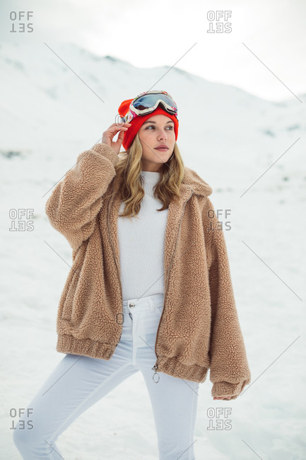 Blonde girl wearing ski goggles and red hat on a snowy mountainside