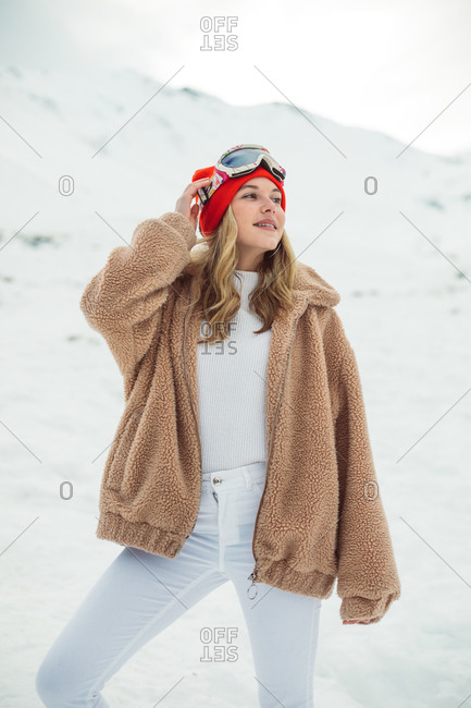 Happy blonde girl wearing ski goggles and red hat on a snowy mountainside