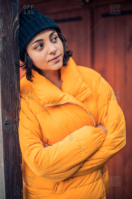 Young woman with short, dark hair wearing yellow jacket and knit hat outdoors