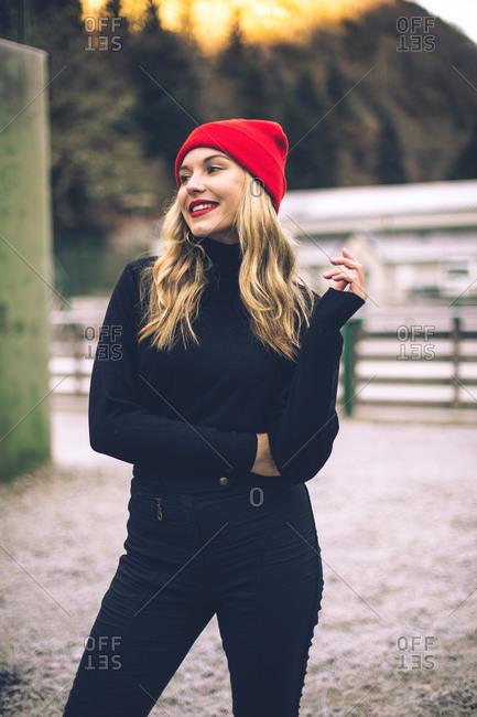 Happy blonde woman wearing red hat in a winter scene