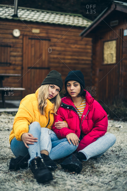 Two young women wearing colorful winter jackets in winter scene