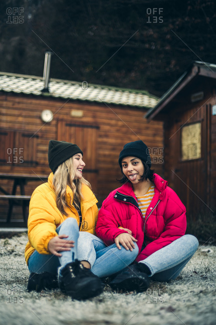 Two young women wearing colorful winter jackets in winter scene making silly faces