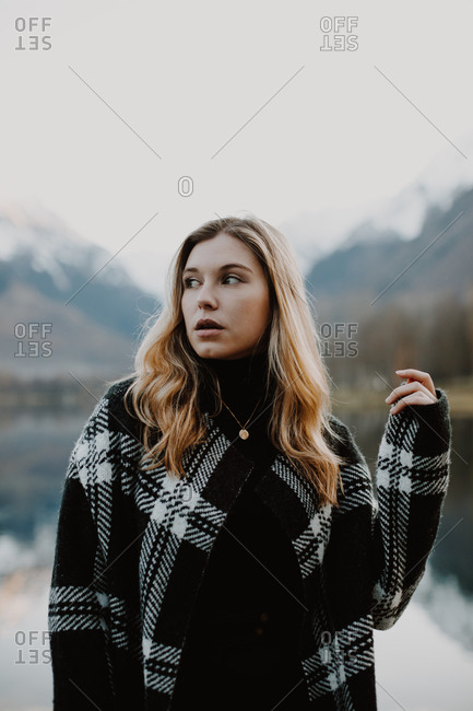 Blonde girl wearing stylish outerwear in a rural setting