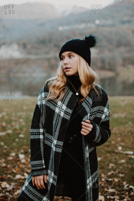 Young blonde woman wearing stylish outerwear on in a rural setting
