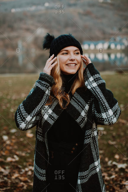 Happy blonde woman wearing stylish outerwear in a rural setting