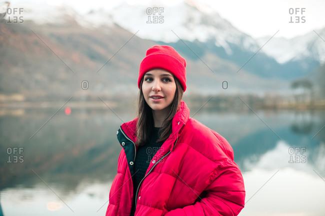 Brunette girl wearing stylish outerwear near a snowy mountain