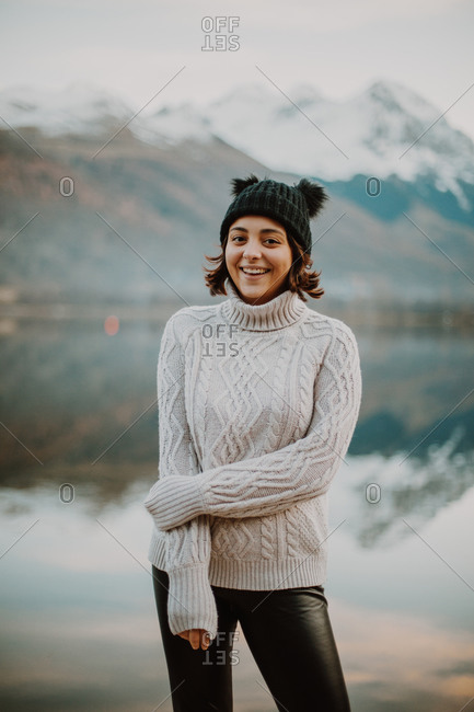 Happy young woman with short, dark hair standing by lake and mountain