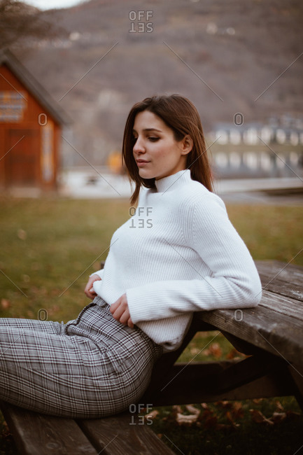 Stylish young woman sitting on old picnic table