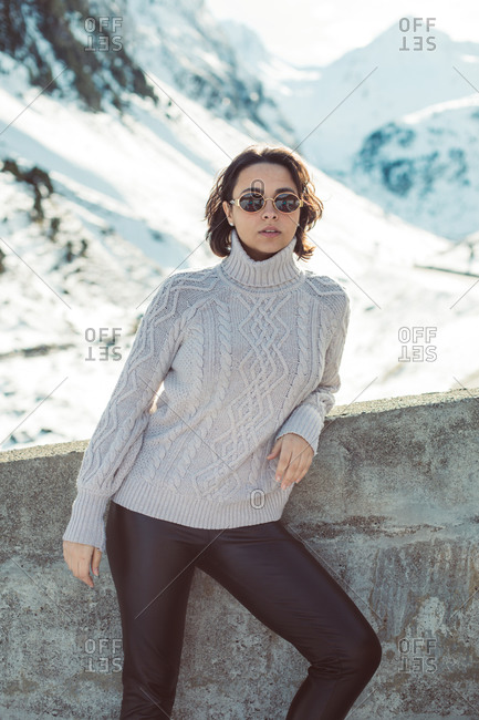 Young woman with short, dark hair wearing sunglasses in snowy mountain scene