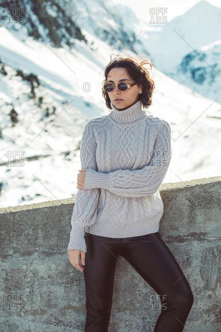 Woman with short, dark hair wearing sunglasses in snowy mountain scene