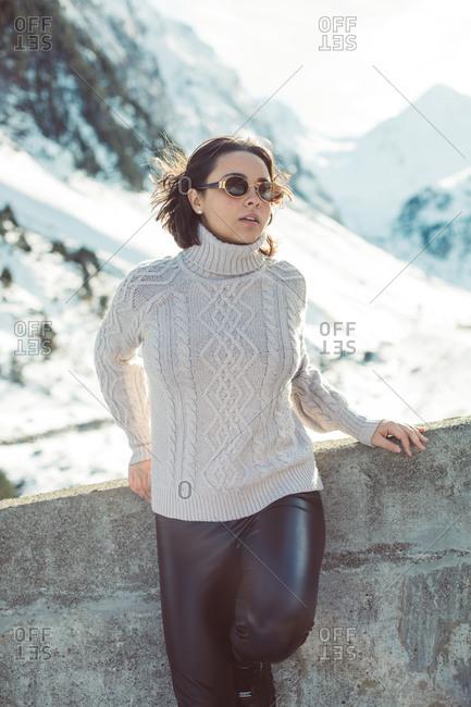 Stylish woman with short, dark hair wearing sunglasses in snowy mountain scene