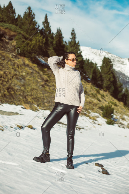 Stylish young woman with short, dark hair wearing sunglasses on a snowy mountain