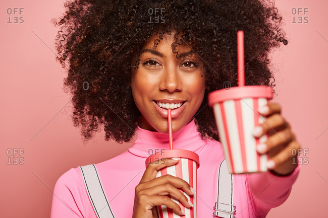 Happy black woman with disposable cup of drink standing against pink background