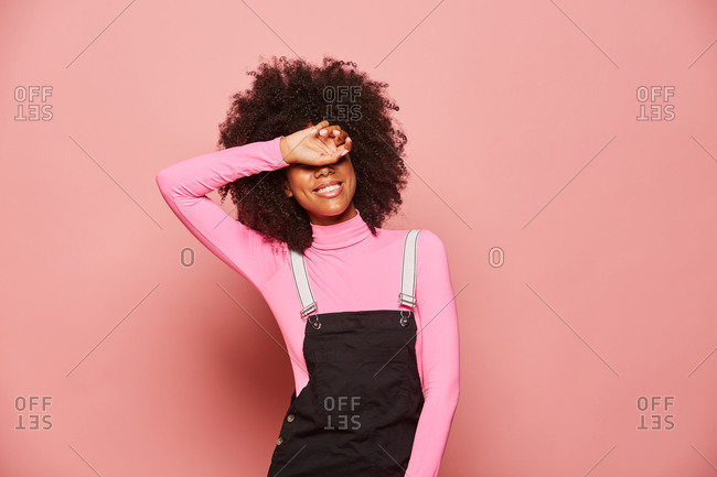 Young African American woman covering eyes with hand