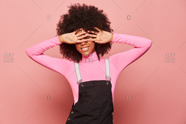 Young African American woman covering eyes with hands