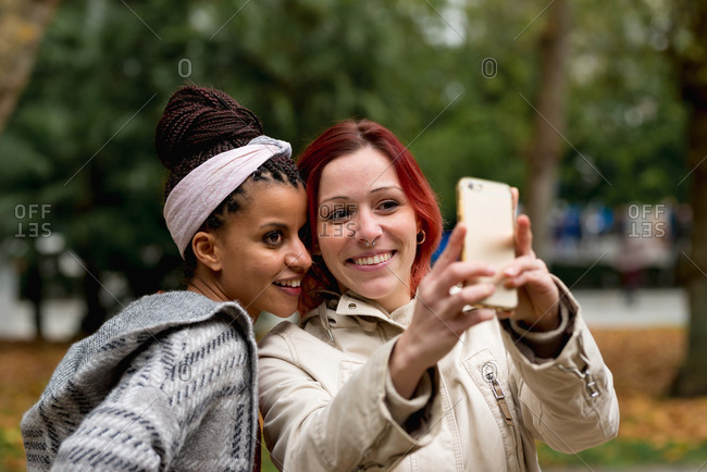 Lovely multiethnic couple of smiling women staying close and taking selfie on mobile phone in autumn park