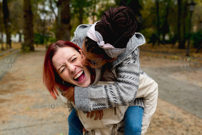 Stylish excited multiethnic couple of young lovely girlfriends having fun together piggybacking in park in sunny day