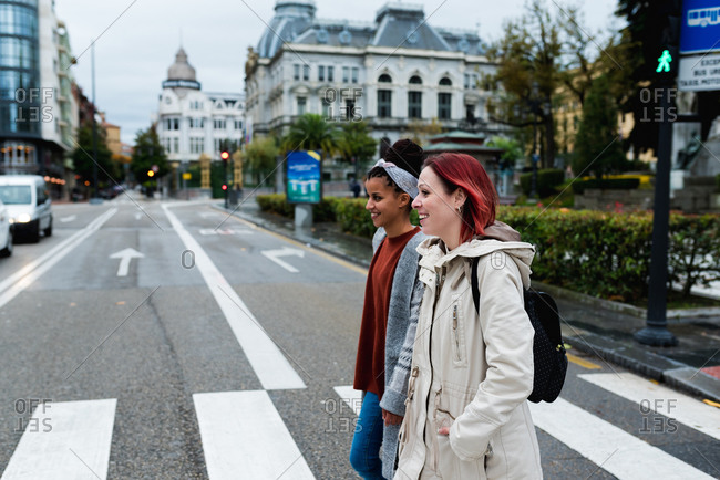Side view of cheerful stylish multiethnic girlfriends walking and crossing marked road in city in gray day
