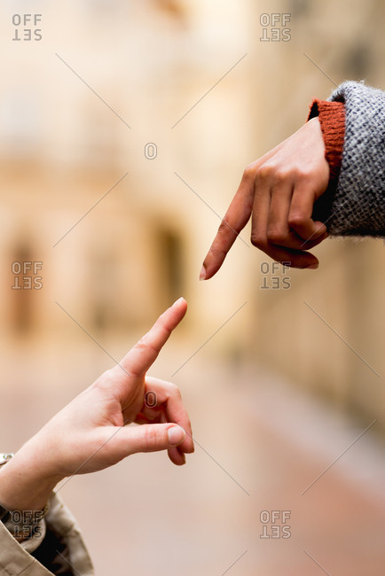 Side view of crop multiethnic stretching hands with finger in street
