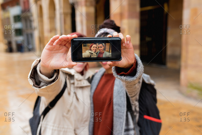 Balanced joyful multiethnic women taking selfie on mobile phone and showing photo at camera in street