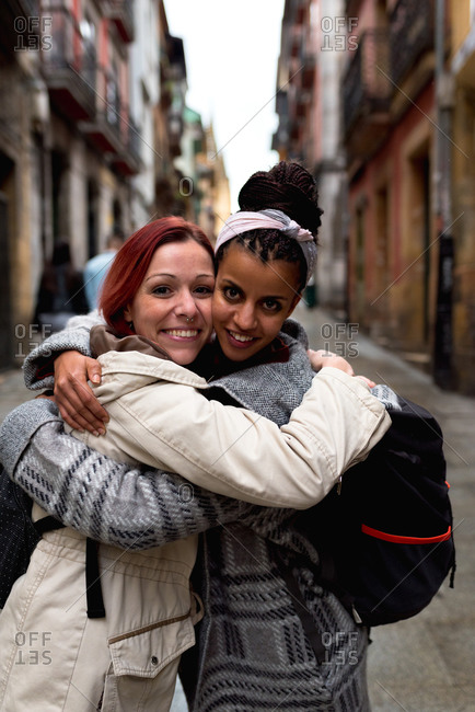 Content multiracial girl friends embracing in narrow street
