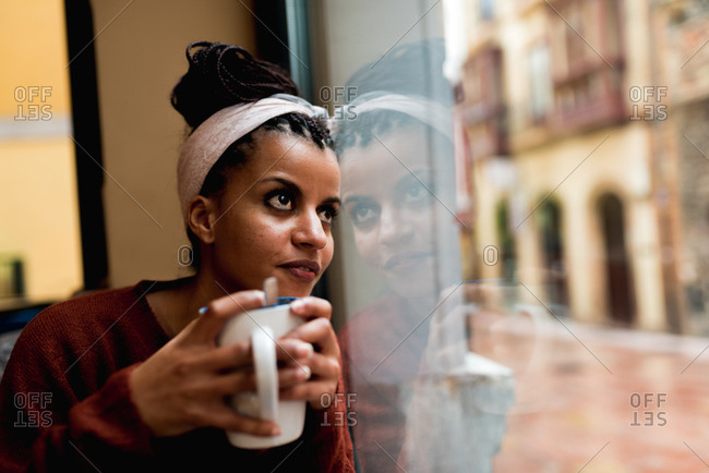 Thoughtful charming African American woman leaning on glass window drinking coffee and dreamily looking away