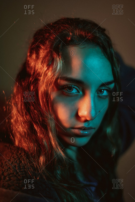 Focused youthful long haired Hispanic female model in casual clothes looking at camera in studio on gray background