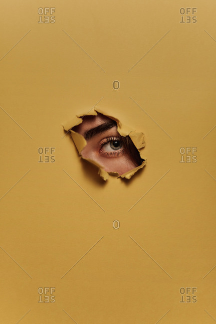 Eye of unrecognizable female model looking through ripped hole in yellow paper