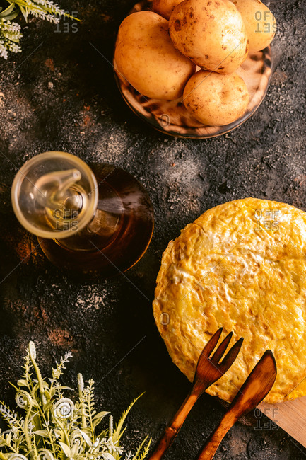Top view of dish of eggs and potatoes near with pitcher of oil on table in kitchen