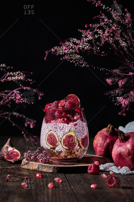 Chia pudding with fresh figs and raspberries including pomegranate and cream in glass at table among pink blossom bunches on black background