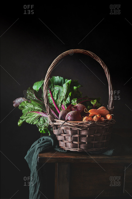 Still life of wicker basket with handle filled of fresh vegetables from garden on fabric and wooden table on black background