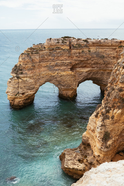 Clean sea water rippling near arched rough cliff on calm day in Portugal