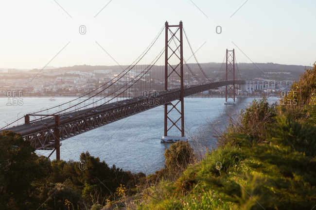 Modern suspension bridge with cars crossing city river against cloudless evening sky in Portugal