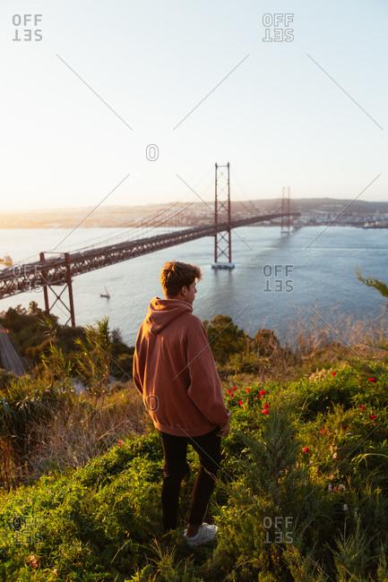 Unrecognizable male admiring bridge over river