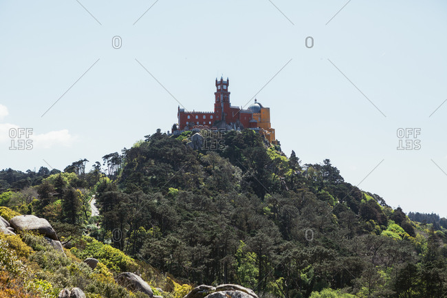 Stone medieval castle located on green rock against blue sky on sunny day in Portugal
