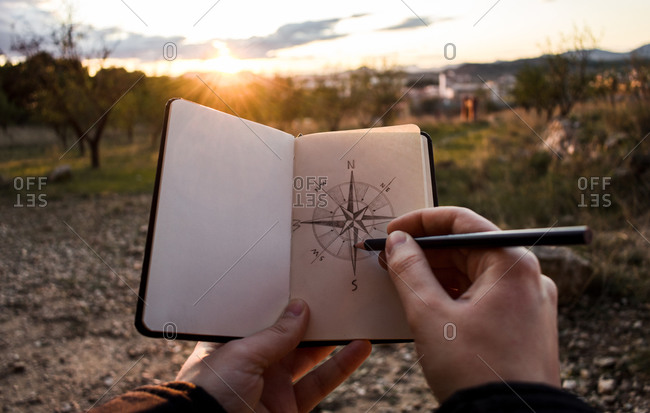Unrecognizable person drawing sketch of compass in notebook during trip through countryside in evening