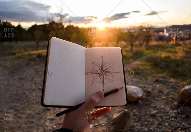 Crop traveler drawing compass during sunset