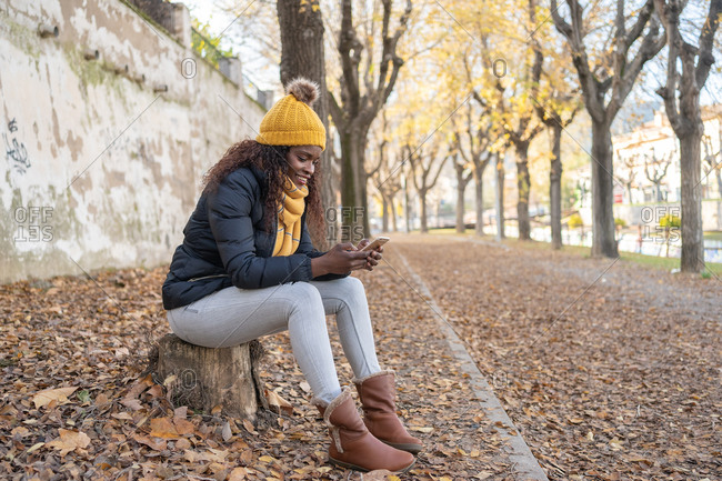 African American woman in yellow hat and warm jacket using smartphone sitting on road with autumn leaves in park