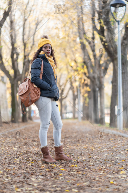 Enthusiastic trendy African American woman in yellow hat and warm jacket with leather backpack and hands in pocket looking at camera with smile on road autumn park
