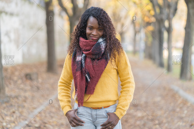 Charming fashion African American woman in a winter scarf with hands in pocket on road with autumn leaves in park