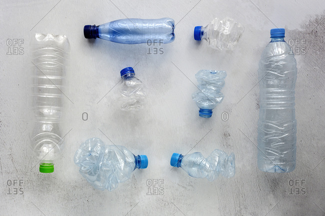 Top view of plastic bottles and boxes arranged on white background surface