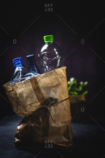 Dirty paper sack with discarded plastic bottles placed on black background
