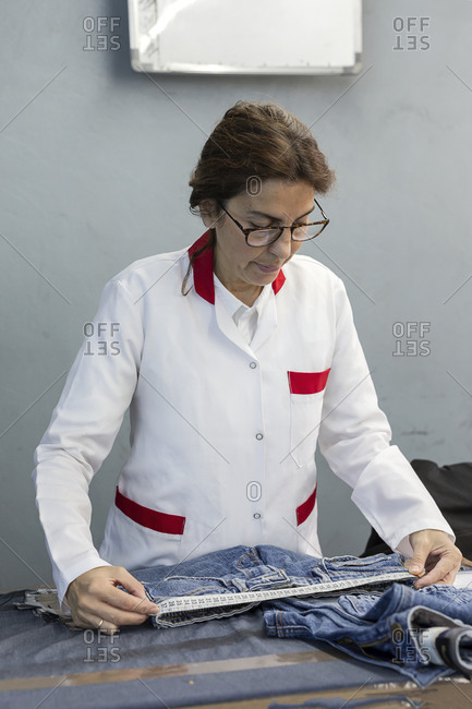 Woman worker in textile factory checking the quality of the garments. Industrial production