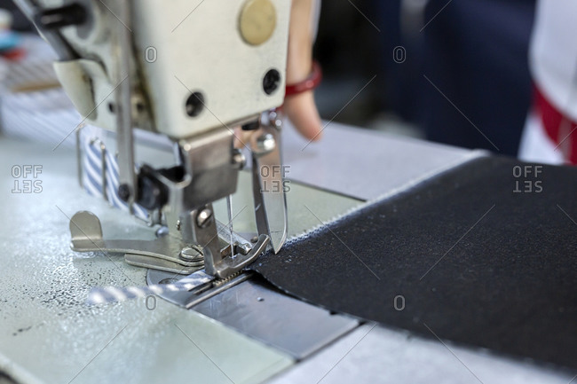 Working woman hands in textile factory sewing on industrial sewing machine. Industrial production