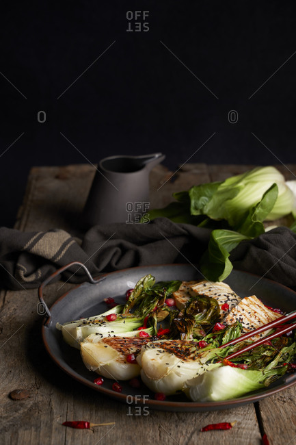 Plate with yummy book choy salad and fried fish placed near napkin on wooden table