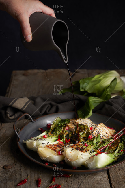 Unrecognizable person spilling soy sauce from jug on delicious book choy salad with fish on wooden table