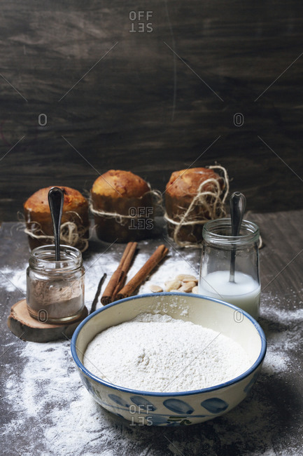 Bowl with white flour and glass jars with cocoa powder and milk placed on table next to spices and ready baked panettone