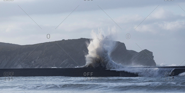 Rough ocean waves crashing on pier with highlands as background during tide