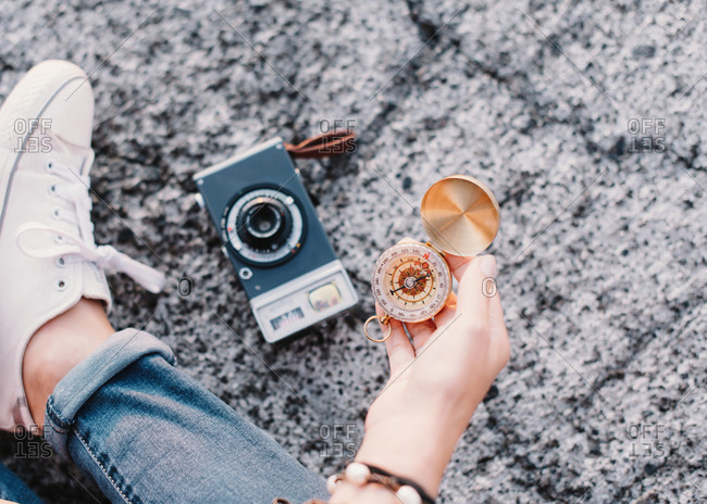 Crop female traveler sitting next to vintage analog photo camera and holding in hand antique golden compass