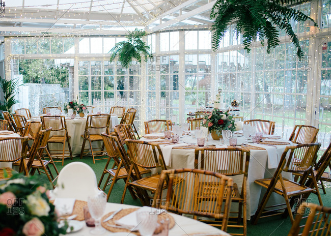 Big spacious room with festive decorated tables and wooden chairs under ceiling with green plants